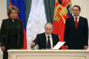 Russian president Vladimir Putin signs law joining Crimea to Russian Federation.
