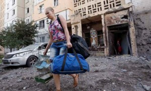 Resident of Donetsk evacuates her apartment after it was struck by Ukraine army shell on July 29, image from Guardian video
