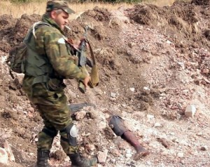 Donetsk self-defense fighter at the site of a mass grave discovered near Mine 22 outside Donetsk. Image from Ruptly news service video report.