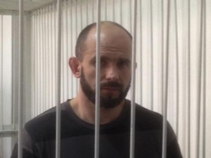 Ex-Berkut commander Dmytro Sadovnyk stands inside a metal cage during a court hearing in Kiev